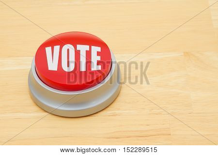 A vote red push button A red and silver push button on a wooden desk with text Vote