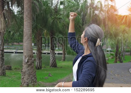 Pretty asian woman feeling satisfied in the park with bright sunlight