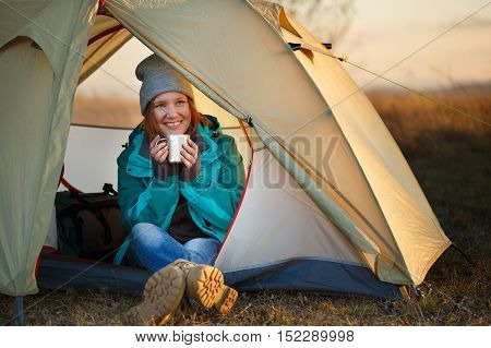 Young beautiful smiling woman in colorful sports wear and trekking shoes sitting in light olive bivouac with metal thermo mug in hands at autumn landscape background with sunset sunlight
