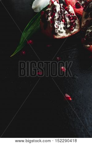 Delicious Pomegranate Fruit And Lilies On Black Background. Stil