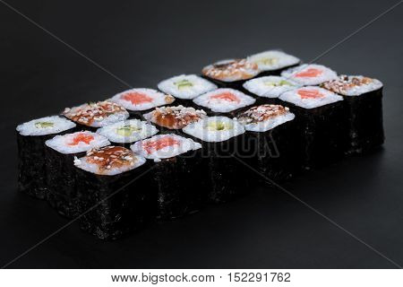 Mix of Japanese nori rolls in on a black background