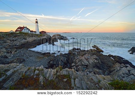Wide shot of rocky cliffs and waves at Portland Head Lighthouse, Maine