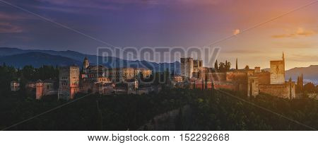 Aerial view of Alhambra Palace in Granada Spain with Sierra Nevada mountains at the background. Evening with sunset colorful sky. Panoramic view