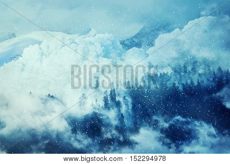 Fantastic winter background with an avalanche in the snowy mountains. Beautiful landscape mist and snowfall in the fir forest. Travel inspiration.