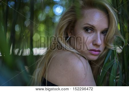 relaxation, beautiful blonde with long black discharge between branches and trunks of vegetation