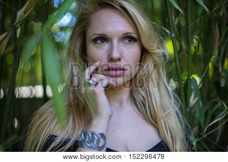 outdoor, beautiful blonde with long black discharge between branches and trunks of vegetation