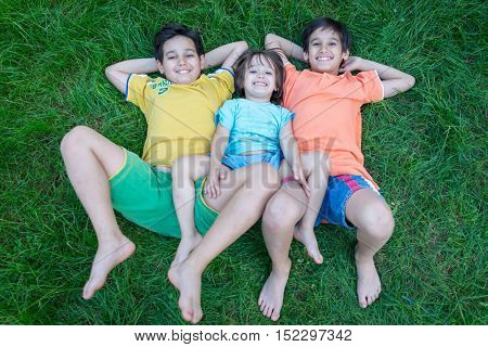Group of cute happy children in summer lying on green grass with feet up