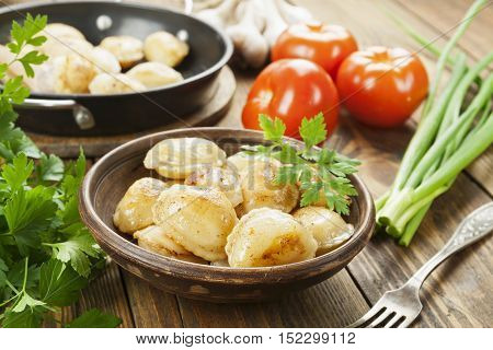 Delicious dumplings in the frying pan on the table