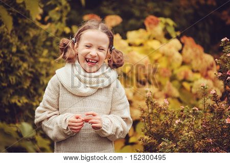 happy kid girl playing in autumn garden near hydrangea bush with dried flowers. Children learning about changing seasons