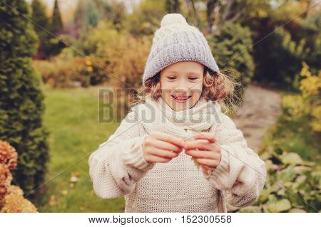cute happy kid girl in warm knitted sweater and hat playing with leaves on late autumn walk on backyard