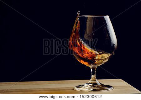 Bohemian glass of cognac on a wooden table