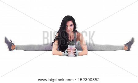Beautiful Sporty Woman In Grey Overalls Sitting In Splits With Shaker, Isolated Over White Backgroun