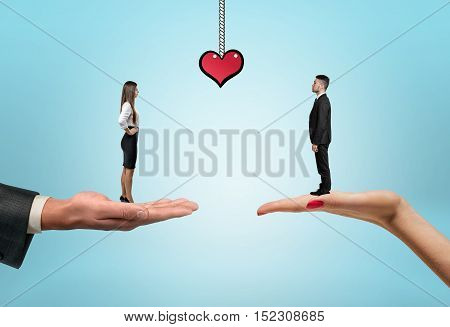 Businessman and businesswoman standing on the women's and men's hands and drawn heart between them. Office romance. St Valentine's day. Love and tenderness. Relationships at work.