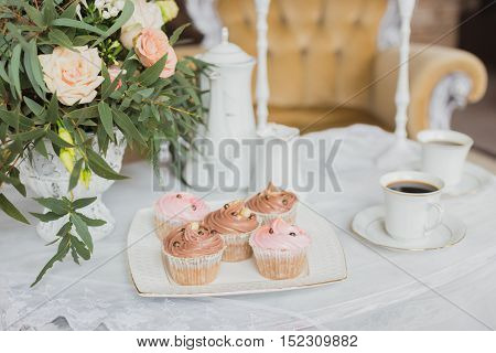 Wedding decorations zone - white table with bouquet, pink candles, cup of coffee and cupcakes