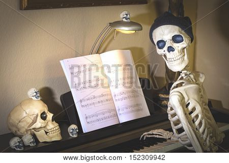 Halloween skeleton and skulls at a piano decorated for the holiday