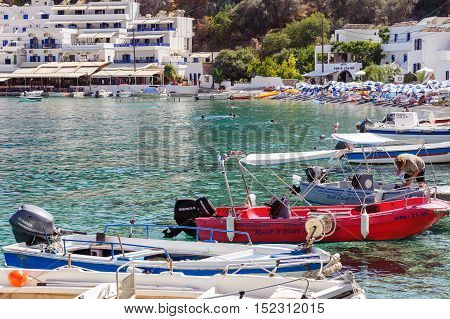 LOUTRO, CRETE, GREECE - JULY 2016: Sea bay of Loutro tona with small beach full of tourists and parked boats on Crete island, Greece