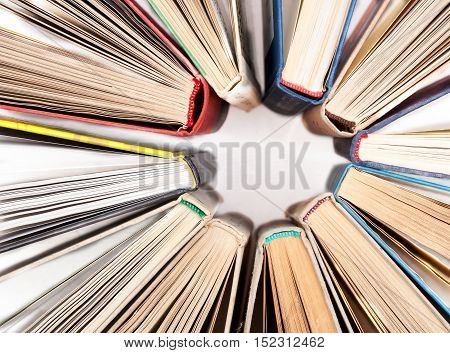 The circle made of old hardback books on white table, top view. Search for relevant and necessary information in a large number of sources during studies or work.