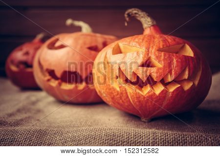 Spooky pumpkins for Halloween party on dark rustic background