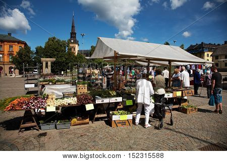 SODERTÄLJE, SWEDEN - JULY 19, 2012: Main Square in Sodertälje with the church in the background and vegetable sales in the foreground on the farmer's market