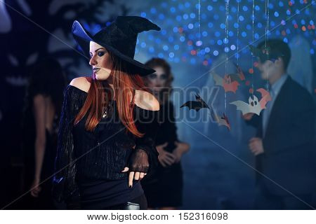 Young woman in witch costume at Halloween party