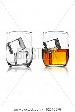 Glasses with whiskey and ice cubes with reflection on white background