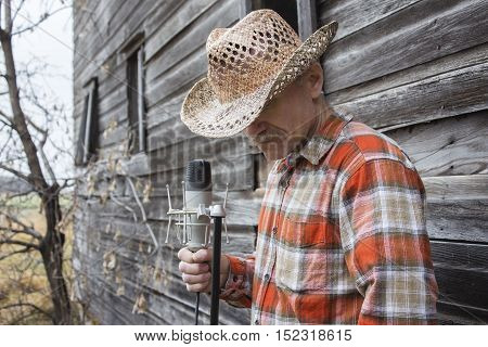 horizontal image of a cowboy singer wearing a cowboy hat and checkered western shirt standing against an old wooden exterior wall holding onto a microphone.