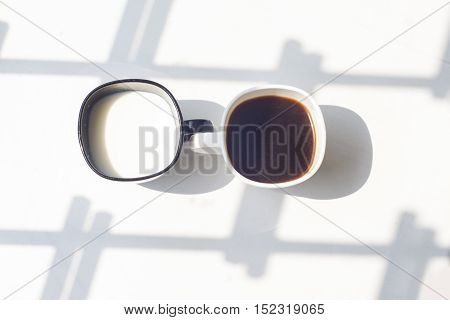 black cup of milk and white cup of coffee on a natural white background, top view