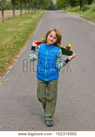 Young cool guy in bright clothes walking with skateboard in the hands