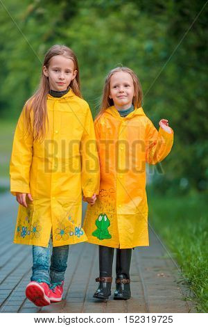 Adorable little girls happy standing under the rain outdoors