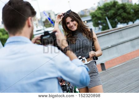 Happy Young Couple Taking Photos In The Street.
