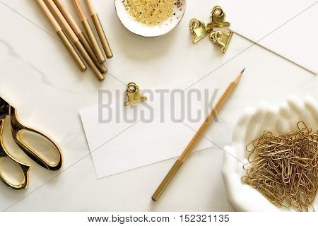 Over head flat lay desk top with gold office supplies and blank notecard for text