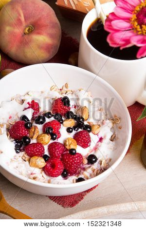 Tasty breakfast: oatmeal with yogurt and fruit on a wooden tray