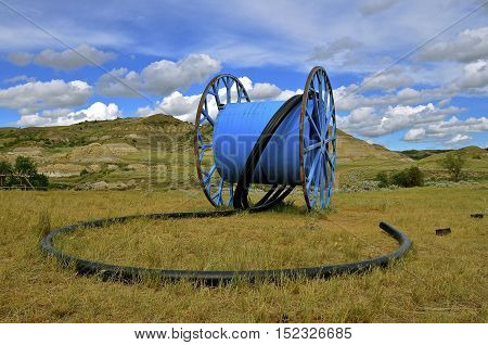 A huge metal reel for holding hose in oil country dwarfs the landscape