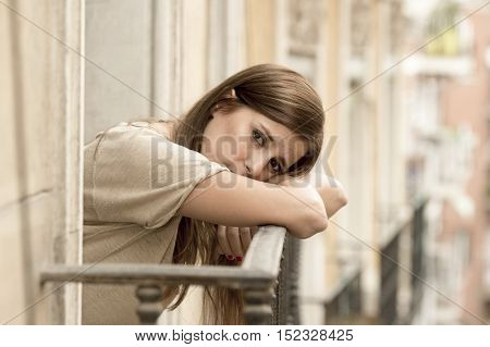 young sad beautiful woman suffering depression looking worried and wasted on home balcony with an urban view in lonely depressed and desperate female concept