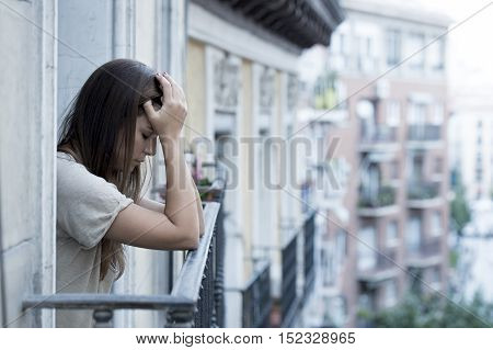 young sad beautiful woman suffering depression looking worried and wasted on home balcony with an urban view in lonely depressed and crying desperate female concept