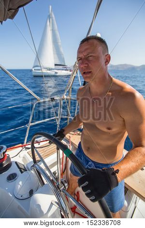 Young man steers sailing yacht boat during the regatta.