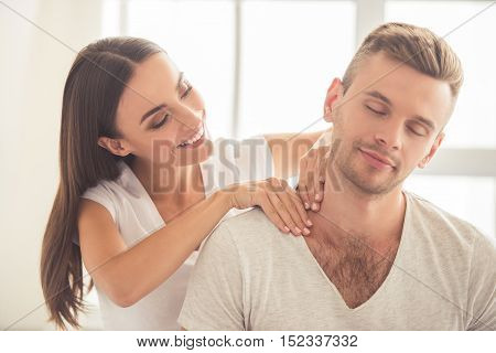 Beautiful young woman is doing her handsome boyfriend massage and smiling while they are resting at home