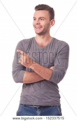 Handsome young man in casual clothes is smiling pointing and looking away isolated on white