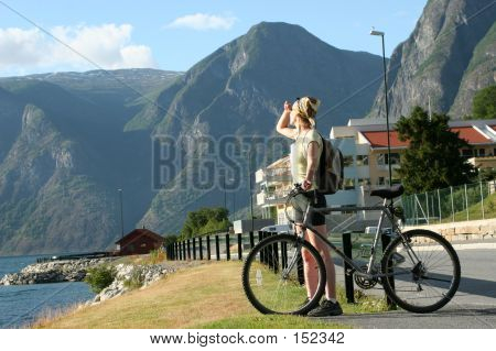 Adult Woman With Bike Looking At The Mountains