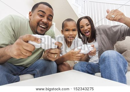African American family, parents and son, having fun playing computer console games together, Father and son have the handset controllers and the mother is cheering the players.