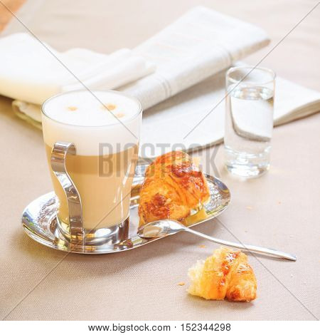 Cup Of Latte With Croissant. Tablecloth Background With Newspaper. Start Of The Day Concept