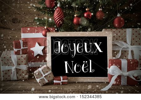 Nostalgic Card For Seasons Greetings. Christmas Tree With Balls And Snowflakes. Gifts Or Presents In The Front Of Wooden Background. Chalkboard With French Text Joyeux Noel Means Merry Christmas