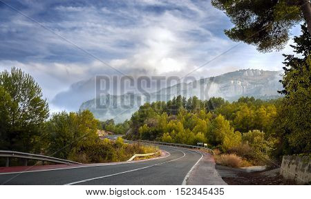 country road at the european alps. Narrow winding road in the mountains at sunset
