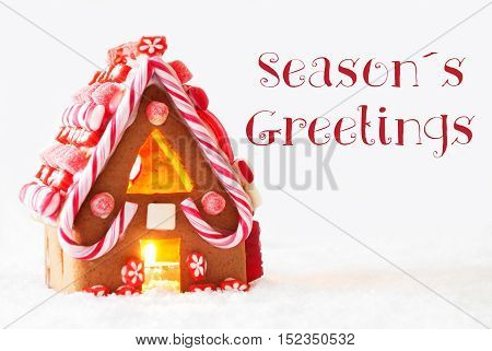 Gingerbread House In Snowy Scenery As Christmas Decoration With White Background. Candlelight For Romantic Atmosphere. English Text Seasons Greetings