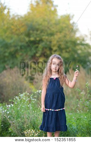 portrait of a sad little girl holding wild flowers