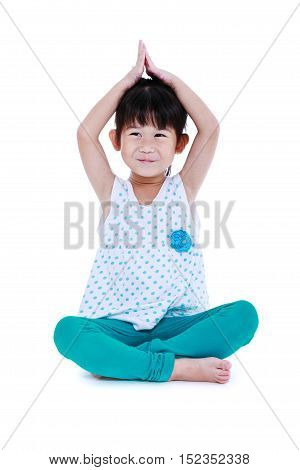 Asian pretty child smiling and doing yoga exercises in lotus pose. Healthy girl practicing fitness at studio. Sports and active lifestyle. Isolated on white background.
