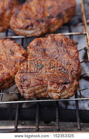 fresh beef meat fillet steak on barbecue grill grid cooked over burned charcoal ready