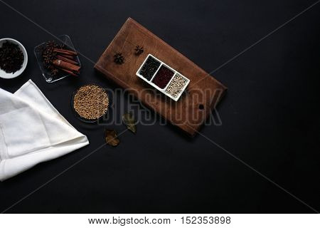several spices in various dishes with cutting board