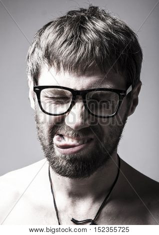 bearded man in glasses plays the fool. crazy man, funny expression.