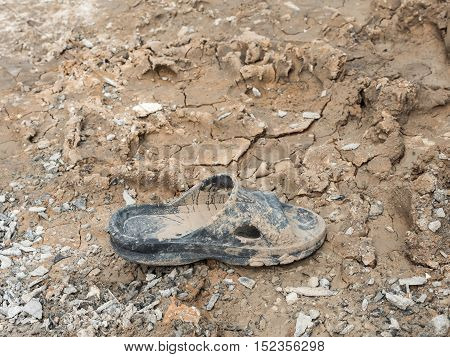 Dirty rubber shoe with the dry mud in the construction site.